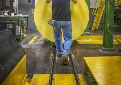 industrial man pushing yellow roll