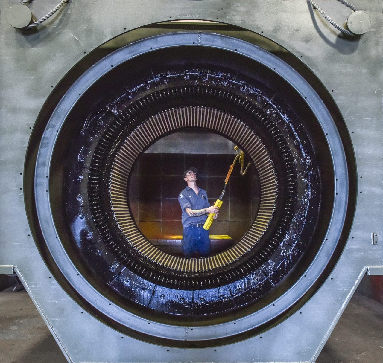 large electric motor with plant technician testing product.