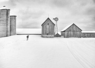 man walking to barn in winter