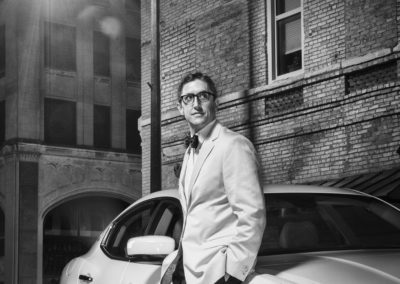 Man in white tuxedo with sports car